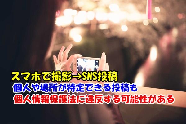街の風景をスマートフォンで撮影する人